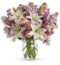 Love is in the air. Or if it isn't, it will be when you surprise her with a gorgeous array of light pink spray roses, fragrant white lilies and other favorites in a sparkling glass vase. You know when she'll love it the most? When it's a total surprise.