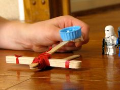 Popsicle stick catapult. I remember a little boy from campus preschool that loved doing this with different materials ;)