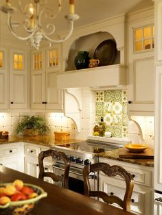"""""""This was a dream client,"""" says designer Bonnie Pressley. """"But she wanted a gas range, and we couldn't get a gas line into the space. Instead, we selected a microwave, electric oven and electric cooktop."""" Custom hand-painted tiles can be seen behind the cooktop, lending more character and color to the electric range."""