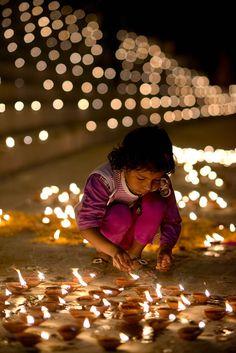 Lighting diyas for Dev Deepawali festival, Varanasi ghats, India