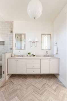 Stunning cream and taupe bathroom features a taupe wood herringbone floor that leads to a cream floating dual washstand donning satin nickel knobs and a cream stone countertop finished with oval sinks and a satin nickel gooseneck faucets.