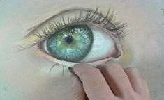 A black pastel pencil is used to paint the eyelashes