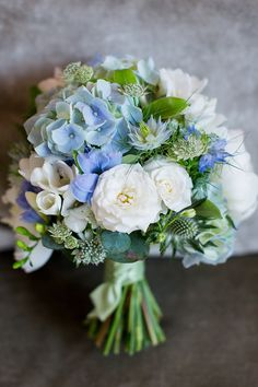 Blue hydrangea, sea holly and love-in-the-mist, and white freesias and roses. More