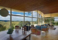 O teto desta casa tem forro de ripas horizontais de madeira ipê que acompanham a ondulação da laje