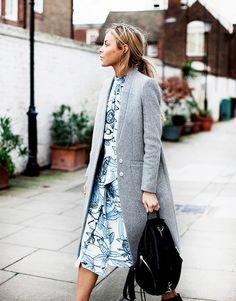 Print dress, grey coat, backpack.