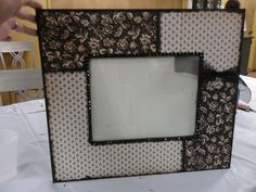 Picture frame made with a plain wood frame, scrapbook paper, black paint and jewels around the inside.