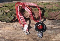 Wunderbarer Upcycling Modeschmuck aus Nespressokapseln. Verziert mit Perlen, Draht,Knöpfen etc. Hier ein Exemplar mit schwarzen Nespressokapseln roten +weißen Perlen gefädelt, im Trachten Stil...
