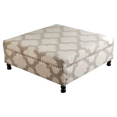 Create a chic focal point in your living room or den with this wood-framed cocktail ottoman, featuring a quatrefoil motif and brass nailhead accents.