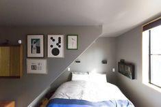狭さが心地よい2階のベッドルーム。畦地梅太郎さんや小板橋雅之さんらの作品を壁に。ベッドヘッドの上にはシャルロット・ペリアンの照明を。