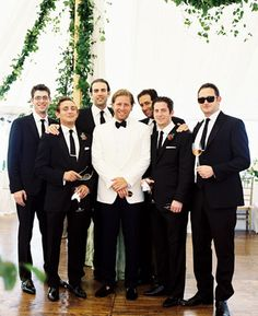 For brynne larsen  Groom in white dinner jacket and bow tie  and groomsmen in black tuxes