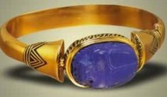"""18 karat gold, lapis lazuli, and black enamel  1"""" x 3/4"""" beetle, 2 1/4"""" diameter  22nd Dynasty, reign of Shoshenq II, Tanis, c.890 BC  The original bracelet is in the permanent collection of the Cairo Museum."""
