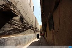 IRAQ, Baghdad : An Iraqi woman walks in a narrow street past electric cables hanged up on the walls on September 21, 2013 in the Iraqi capital Baghdad. Iraq is one of the world's leading oil producers, but its electrical infrastructure, heavily damaged during the war, is obsolete. AFP PHOTO SABAH ARAR