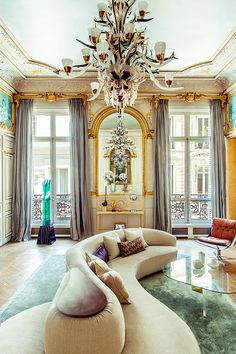 Un lustre monumental, en verre de Murano, trône au centre du salon. C'est une pièce de l'artiste franco-suisse Aristide Najean. Au fond, la console est attribuée à Jacques Adnet. La sculpture en Plexiglas vert est une œuvre de Jean-Claude Farhi. © Matthieu Salvaing