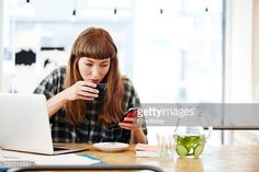 Stock Photo : Girl drinking coffee checking her phone
