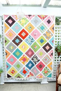 "The ""violet craft"" blogger spent a year collecting Denyse Schmidt's out of print Flea Market Fancy collection until she had all the fabrics. She had just barely enough of some of them to make the quilt. Lovely white sashing between the squares...I'd probably have gone with black, and probably I'd have been wrong."