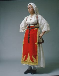 "Central Greece: Desfina costume, worn in several villages ""Female Desfina costume from the Phokis region as it developed in the early 20th c. in a very simple composition. It has two chemises one on top of the other, a short sleeveless white coat kept in position with a characteristic of the region dark blue striped belt, as well as the narrow long apron with yellow or gold cord embroidery. Last but not least a white butter muslin kerchief ornamented with small pompoms or 'chenille' fringe."""
