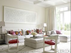 The family room in fashion designer Tamara Mellon's Hamptons home features a sofa and daybed by Poliform, a pair of Karl Springer armchairs bought on 1stdibs, and a velvet-covered ottoman by Room & Board; the large-scale print is by Bridget Riley, the pillows are by Madeline Weinrib, and the rug is by Stark. Tour the rest of the home.