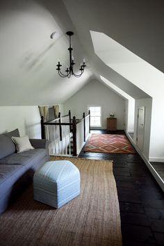 屋根裏空間の変形の窓からはいる陽ざしがつくる、柔らかな照明器具や階段の手すりの影が美しいお部屋。様々な色彩のファブリックやソファが優しい空間をつくっています。