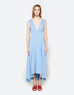 Flowy dress from Farrow in Blue. Deep V-neckline. Thick straps with gathering at shoulders and bust. Sleeveless design. Concealed back zip closure. Fitted through waist. Long flared skirt. Stepped hem. Unlined.   • Fine line twill • 100% rayon • Hand