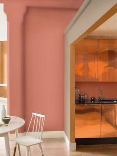 Deze kamer straalt warmte uit en geeft een mooi contrast in combinatie met de koperen wand.