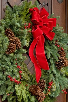 Natural materials are the easiest to work with for an exterior display. Embellishments such as holly, berries, or small ornaments, add a punch of color. A bright red velvet bow on a fir wreath is a classic we love.
