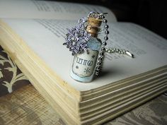 """2ml glass vial filled with pale blue and white glitter with aged/antiqued """"Let It Go"""" label and silver snowflake charm.  Bottle measures 35mm x 16mm (1.38 in x 0.63 in) and comes on 18"""" silver ball-chain.  Bottle cork will be secured in place with waterproof sealant to prevent leakage and/or ..."""