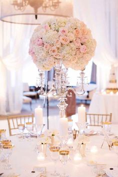 Ice/crystal candelabra with large flower topper featuring hydrangeas and roses and pillar candles on crystal columns. Stunning centrepiece design.   WedLuxe– An Elegant Black Tie Wedding Planned by the Bride | Photography by: Lucida Photography Follow @WedLuxe for more wedding inspiration!