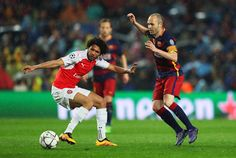 Mohamed Elneny of Arsenal and Andres Iniesta of Barcelona compete for the ball during the UEFA Champions League round of 16, second Leg match between FC Barcelona and Arsenal FC at Camp Nou on March 16, 2016 in Barcelona