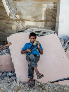 See Inside Gaza with Photographer Peter van Agtmael - LightBox - A child with an Israeli mortar shell in a neighborhood destroyed near Rafah, southern Gaza.