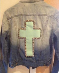 Denim jacket with a mint green cross on the back. I can't forget the gold studs on it as well(: <3