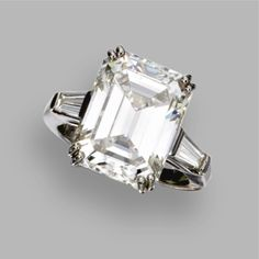 DIAMOND RING The emerald-cut diamond weighing 8.51 carats, flanked by 2 tapered baguette diamonds, mounted in platinum