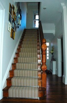 A beautiful staircase that makes use of a runner and stair rods.