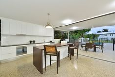 The polished concrete floor throughout the living areas create a modern tropical home. Polar white cabinetry with timber laminate benchtops add to the simplistic modern home. Modern Tropical, Tropical Houses, Building Companies, Polished Concrete, Concrete Floors, Living Area, Custom Design, New Homes, Construction