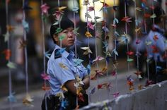 A police officer stands behind origami paper cranes at a protest site after some barricades were removed, at the commercial area of Causeway Bay in Hong Kong October 14, 2014.  REUTERS-Carlos Barria