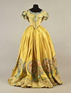 TRAINED SILK BALLGOWN, attributed to JULIA GARDINER TYLER, c. 1852 - Tan 2-piece having back-lacing bodice with deep front and back points, and short puffed sleeve, decorated with blue ribbon, lace and metallic gold thread, bodice and skirt center panel embroidered in blue and cream silk floral, the skirt having a series of scalloped ruffles, set in yellow silk appliquéd with a polychrome floral on pink set within blue braided wreaths with bows, tan scalloped hem ruffle.  whitakerauction