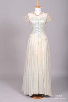 Designed in the 40's, this unbelievable vintage wedding gown is done in an sheer lace embroidered net over a Robin's egg blue silk taffeta lining in the bodice and a sheer net over the same silk taffe