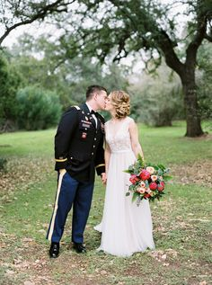 A bride a groom hold hands and kiss at outdoor wedding venue Kindred Oaks near Austin, Texas // Jen Dillender Photography