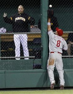 Philadelphia Phillies center fielder Shane Victorino (8) cannot catch a ball hit by Pittsburgh Pirates' Rod Barajas that went for a double in the 10th inning of the baseball game on Saturday, April 7, 2012, in Pittsburgh. Barajas was replaced by Michael McKenry as a pinch-runner who later scored as the Pirates won, 2-1 in 10 innings.