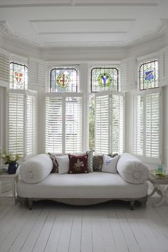 Simple, white living room look with large bay window shutter dressing. We love how traditional period features have been brought up to date with white painted floorboards, white tall ceilings and a chaise longue sofa to dress the room. Bay Window Bedroom, Bay Window Benches, Bay Window Decor, Bay Window Living Room, Wooden Window Shutters, White Shutters, Dining Room Windows, Bay Window Curtains, Bay Windows