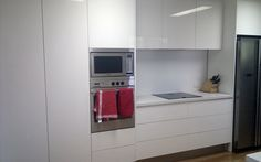 Gloss white with push to open cupboards and drawers