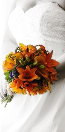 Bold orange lilies contrast with sunflowers and blue delphinium