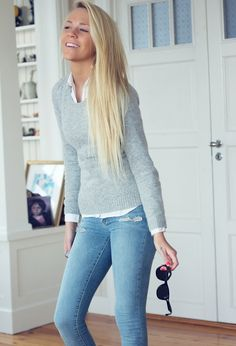 Soft grey sweater layered over a white collared polo and paired with blue jeans.