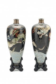 Namikawa Yasuyuki (1845-1927) c. 1890, Meiji period. A pair of early and large Namikawa silver-wire cloisonné leaf-shaped vases with original wooden stands. Each vase depicts an olive or cream colored dragon flying through a night sky consisting of a black cloisonné ground filled with silver-wire clouds, surrounded by ribbon-like flames, above blue and white crashing waves. A ring of black, brown and blue lappets circles the foot ring and floral, zigzag, and cloud borders encircle the…