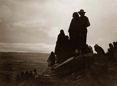 Here for your perusal is an original photograph of Hopi Indians Watching the Morning Races. It was created in 1905 by Edward S. Curtis.    The photograph illustrates a Group of Hopi Indians looking into the distance at the valley floor where a horse race is underway.    We have compiled this collection of photographs mainly to serve as a valuable educational resource. Contact curator@old-picture.com.