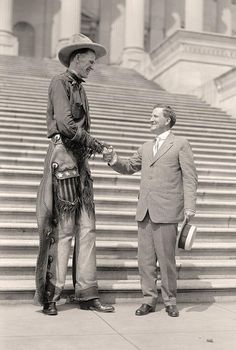 "Ralph E. Madsen, the Tall Cowboy. at Capitol in Washington, D.C., Shaking Hands With Senator Morris Sheppard of Texas in 1919. Known simply as ""Tex"", Ralph E. Madsen, born in 1897, grew to be 7'6"" and was considered the tallest man in the United States at that time. He spent most of his life on a ranch in Texas, acquired veterinary skills and was an authority on horses, sheep, cows and pigs. He eventually traveled to every state, Mexico and Canada, always accompanied by his minature horses."