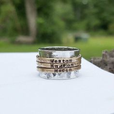 Custom hand stamped gold and silver spinner ring. Main band is fine sterling silver with 14k gold filled spinner ring bands. Narrow bands are hand stamped with your choice of text and spin freely around the wider 1/2inch band. 925 Sterling silver Bands are 2mm wide and text is very