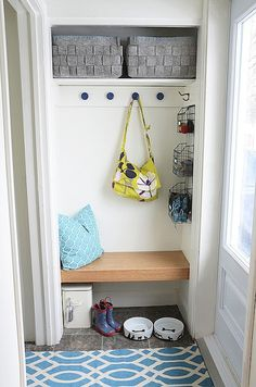 source: Nalle's House Hall closet transformed into mudroom. Closet mudroom features West Elm Felt Baskets on top shelf and row of hooks and wire wall-mounted baskets from Homesense. Mudroom closet with built-in floating bench with turquoise pillow and turquoise blue trellis rug layered over slate tile floor.