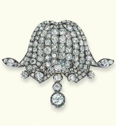 AN ANTIQUE DIAMOND BROOCH, CIRCA 1890. The pavé-set old-cut diamond lily with collet stamen and articulated diamond three-stone fringe, mounted in silver and gold, 6.0 cm wide. #antique #brooch