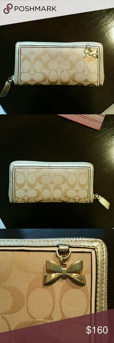 Coach Signature Bow Charm Accordian Zip Wallet Beautiful Coach zip wallet. Cream color with pale pink and gold trim. New, carried 2 or 3 times at most and in perfect condition! Coach Bags Wallets