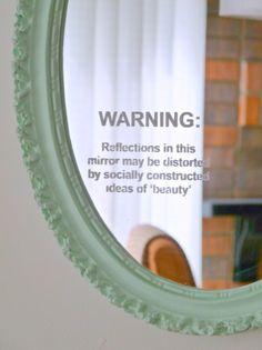 """Advertencia: Los reflejos en este espejo pueden estar distorsionados por las ideas  de """"belleza"""" socialmente construidas."""